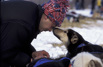 Dog and musher touching noses in winter